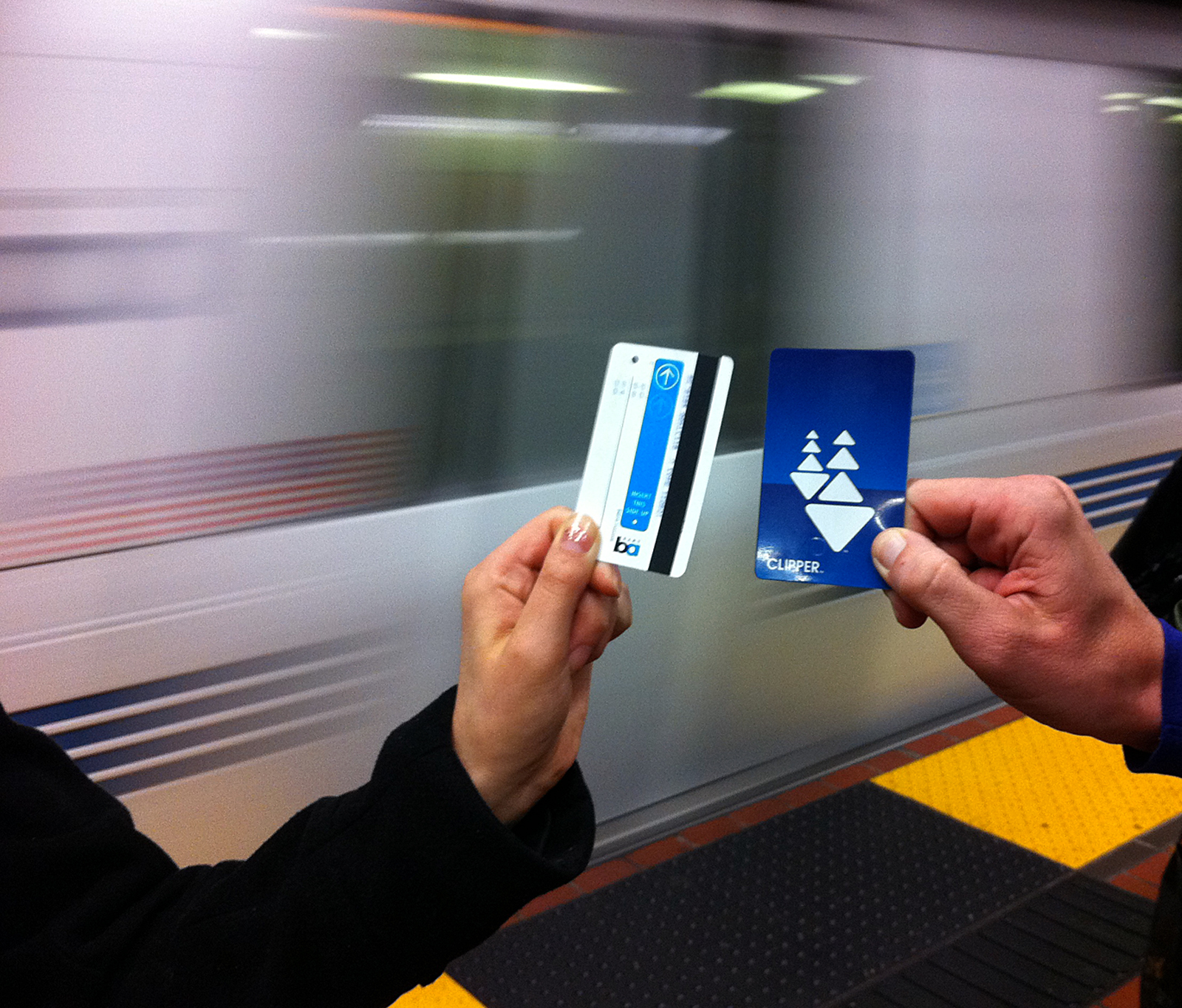 The blue paper BART ticket held next to a Clipper card.