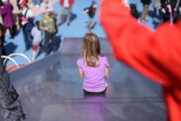 A girl gets ready to go down the big slide at the Helen Diller Playground which reopened Saturday.