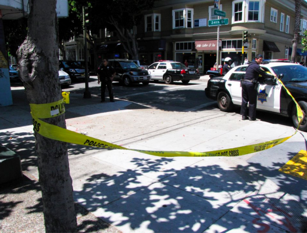 A police officer corners off a section of 24th and Harrison Street after a masked man opened fire. Photo by Francisco Barradas.