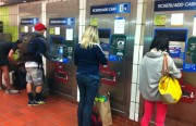 Commuters use the 16th St. BART kiosks ahead of their trip.