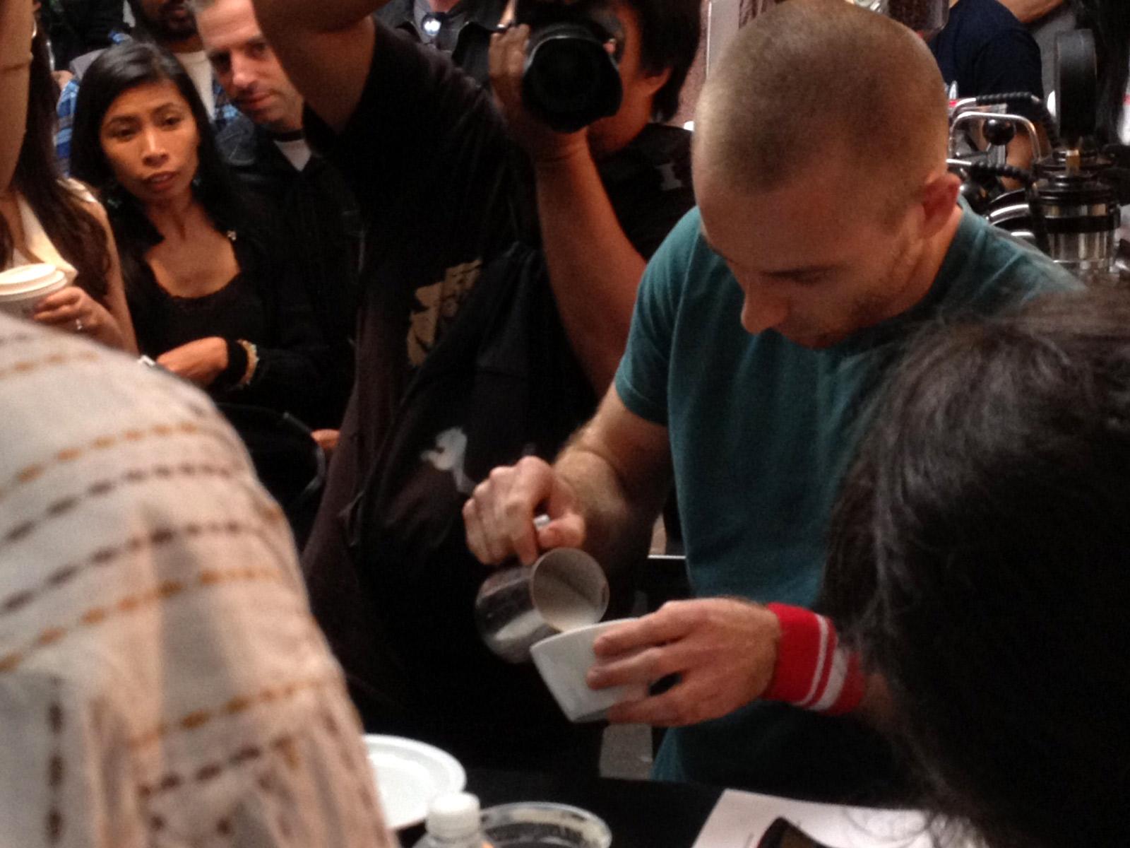 Image shows a man pouring latte art