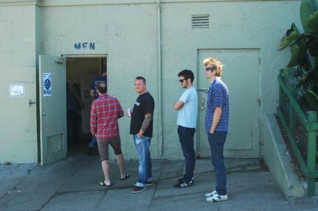 Image shows men standing in line.