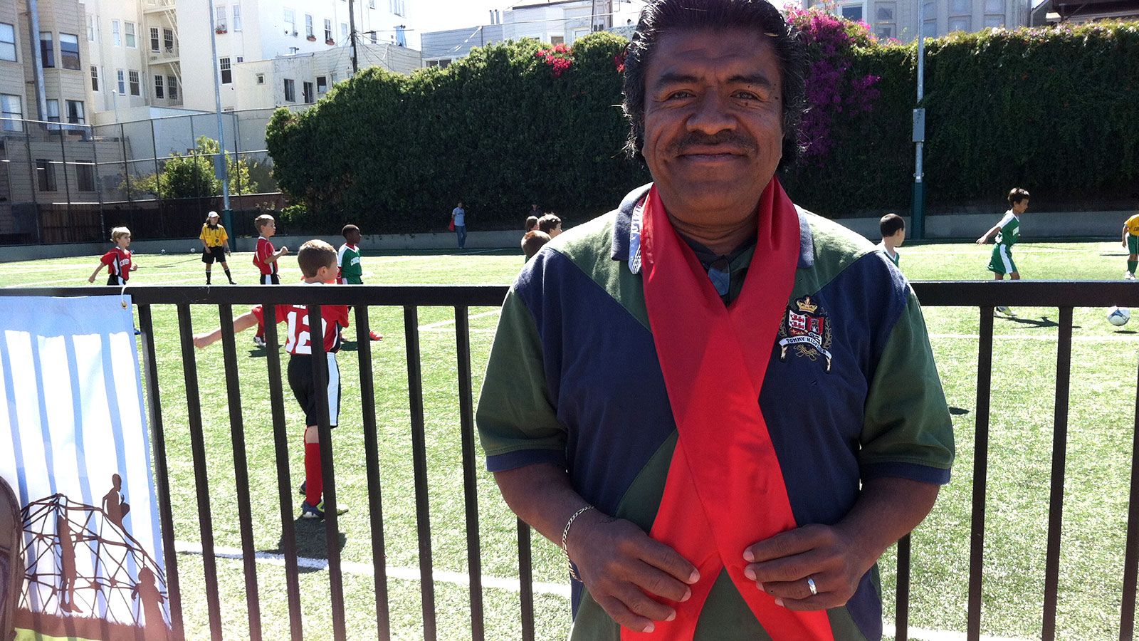 Cesar Hernandez wears the cast-off ribbon families cut during reopening ceremony for Mission Playground.