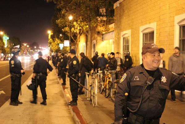 SFPD officers mill around the Mission Police Station Friday night after demonstrations in the Mission. Photo by Mateo Hoke.