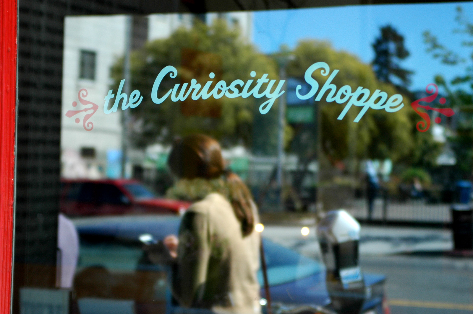Photo show a woman walking by Curiosity Shoppe