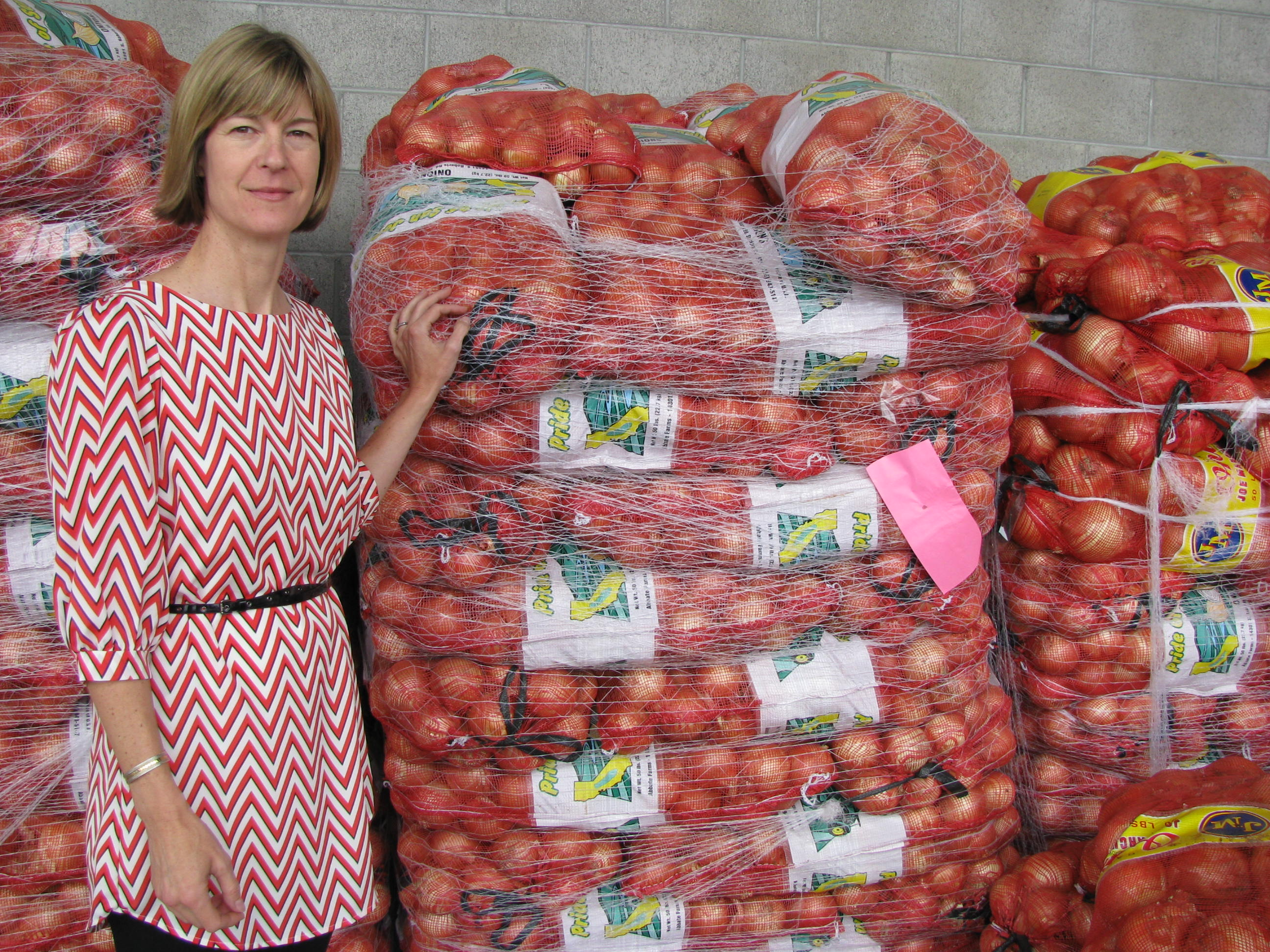 Teri Olle stands next to pallets of tomatoes at the San Francisco and Marin Food Banks Headquarters.
