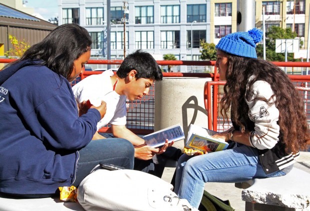 Students discussing a book outside