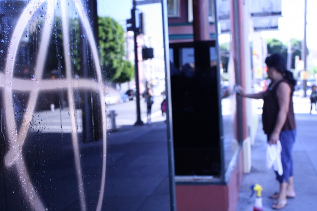 A woman cleans anarchy graffiti symbols off her business windows.
