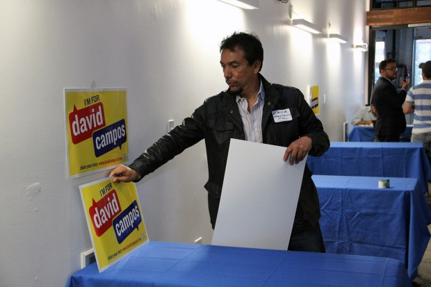 Host Erick Arguello, President of the Lower 24th Street Merchants and Neighbors Association, hangs up signs at a fundraiser for District 9 Supervisor David Campos at 780 Cafe.