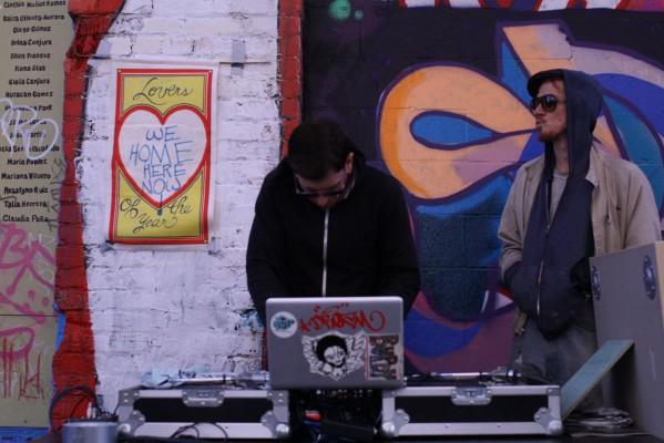 A DJ preparing his set while his friend looks down the alley.