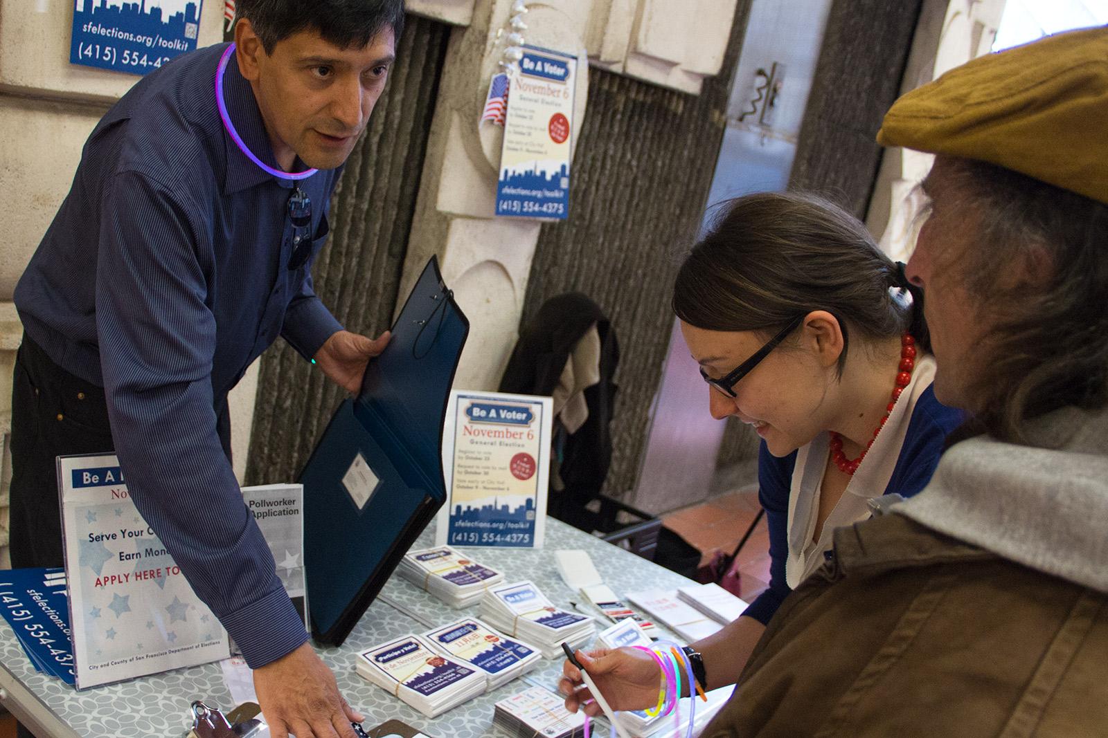 Nestor Cuellas asiste a residentes municipales a completar las solicitudes de registro de votantes en la estación de BART de la calle 16 el 22 de octubre, el último día para registrarse para votar en la elección general del seis de noviembre.