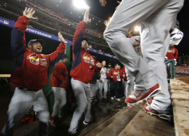 Cardinals' Skip Schumaker (left) and manager Mike Matheny (center) congratulate Carlos Beltran (foreground right) after Beltran and Adron Chambers both scored on a single by Daniel Descalso to tie the game in the ninth inning during Game 5 of the National League Division Series between the St. Louis Cardinals and the Washington Nationals on Friday, Oct. 12, 2012, at Nationals Park in Washington, D.C. Photo: Chris Lee, Post Dispatch / AP