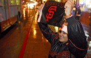 """Raylene Lopez, age 19, of Bayshore, shows her Giants pride by cheering on passing cars along Mission Street. """"Everytime the Giants win my brother and I come to the Mission to celebrate because this is where it's at,"""" said Lopez."""