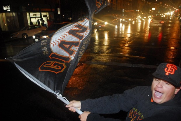Jose Torres waves a Giants flag along Mission Street where many fans turned to show their pride after the Giants defeated the Cardinals in the National League Championship Series.