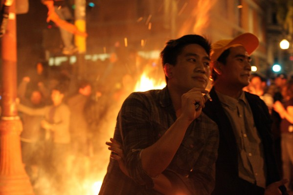 Fans pose in front of the fire on 19th and Mission streets. Photo by Rigoberto Hernandez