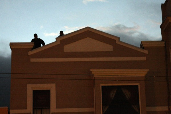 Two officers stand on the roof of a vacant Castro Street building after following protesters there on World Homeless Day. Photo by Rigoberto Hernandez