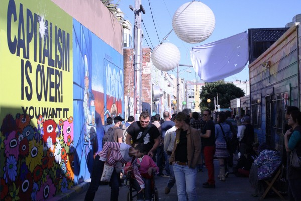 """""""CAPITALISM IS OVER,"""" reads a mural overlooking the crowd."""