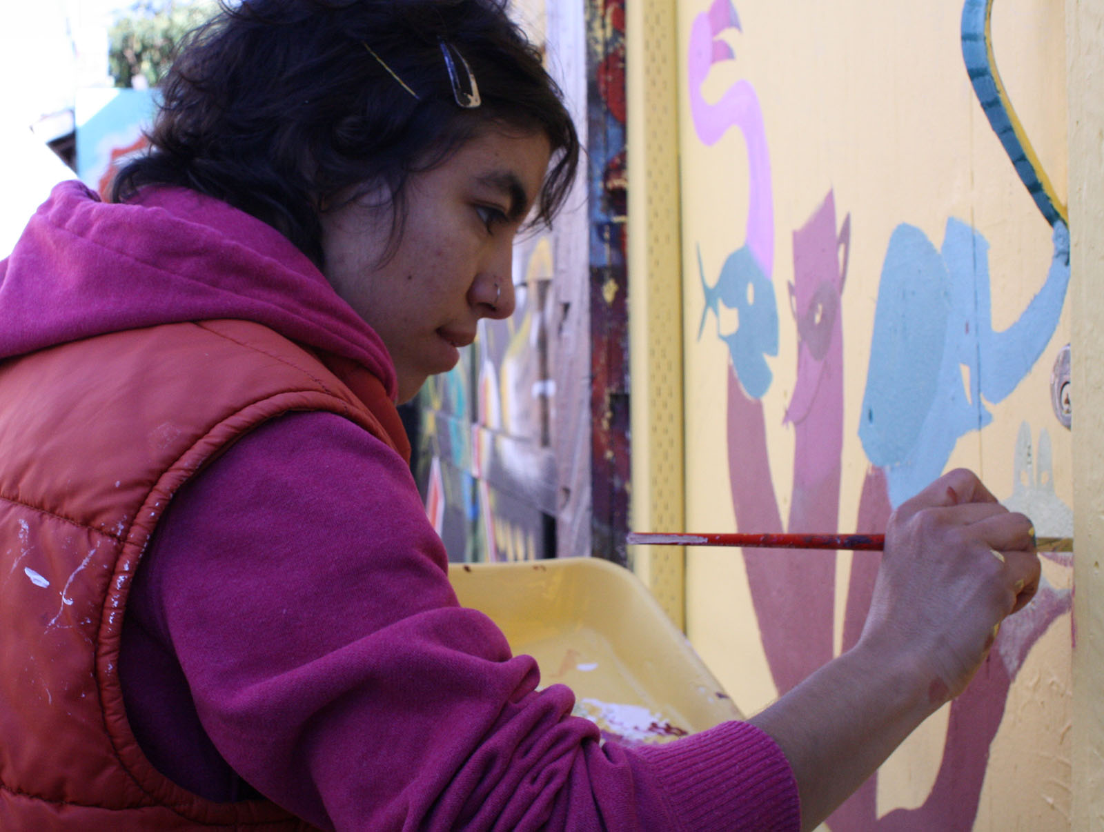 A woman paints a new mural in the alley.