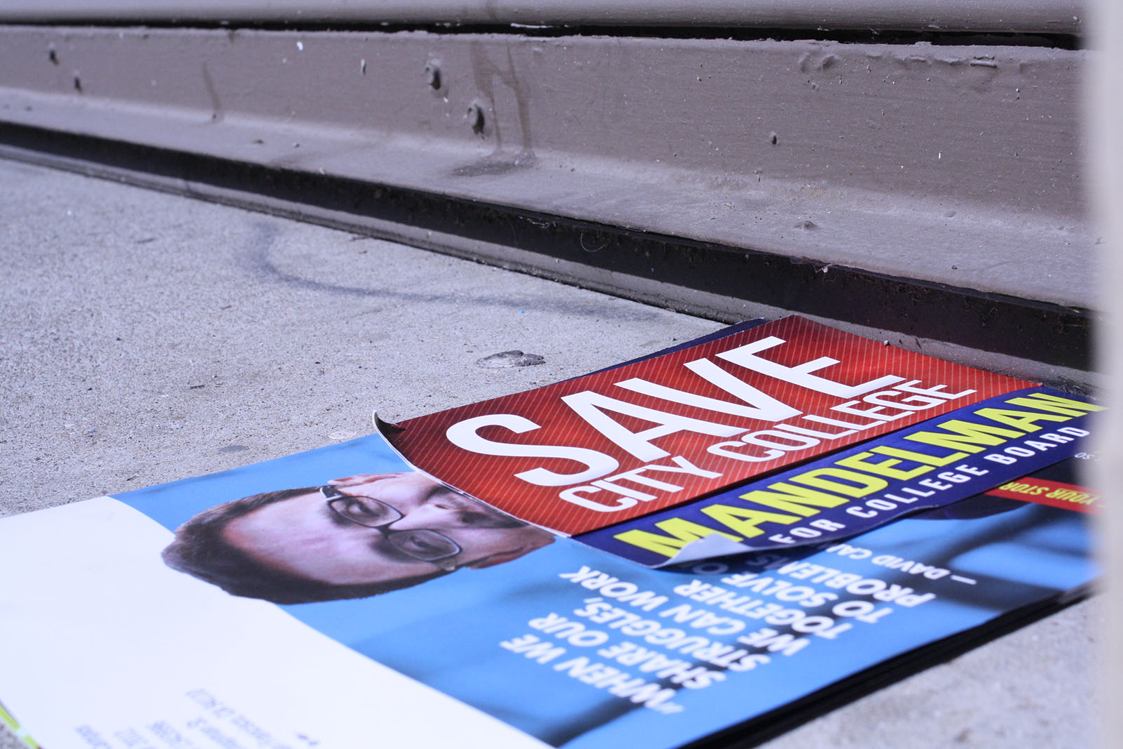 "Supervisor Campos' flyer under a ""Save City College, Mandelman for College Board"" flyer on the sidewalk."