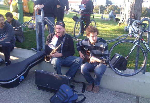 """A few protesters perform the song """"Come Together"""" by The Beatles. Photo by Carly Nairn."""