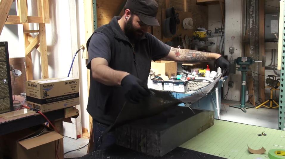 Image shows a man putting carbon fiber into a guitar mold.