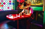 Don Miguel de Los Angeles no McDonalds sits at a table holding a drink