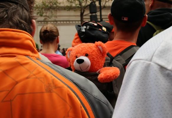 A fan carries an orange bear in his backpack. Photo by Alicia Avila.