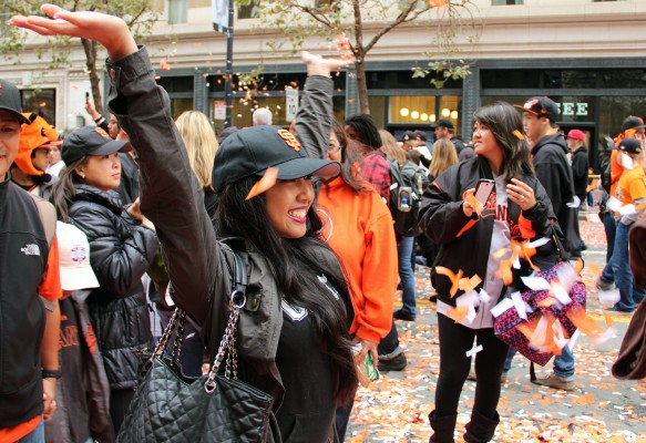 A woman smiles as confetti falls on her head on Market Street. Photo by Jamie Goldberg.