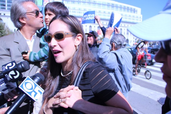 Eliana Lopez, wife of Sheriff Ross Mirkarimi, talks to the media as she arrives at the noontime rally before the Supervisors' hearing. Photo by Alana Levinson.