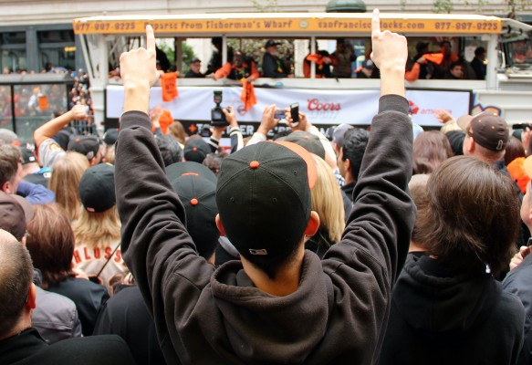 A fan cheers as floats pass him on Market Street. Photo by Jamie Goldberg.