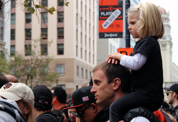 A girl sits on a man's shoulders to watch the parade. Photo by Alicia Avila.