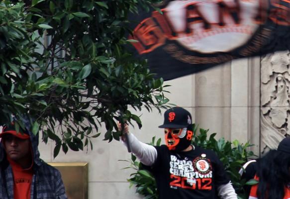 A fan waves a Giants flag on Market Street. Photo by Jamie Goldberg.
