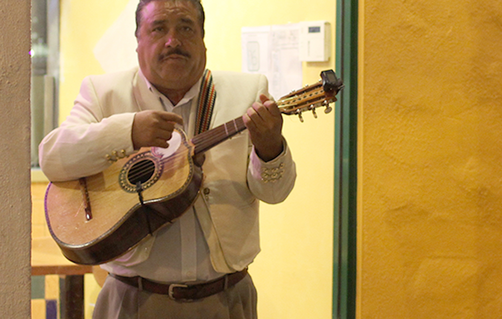A mariachi plays his guitar.