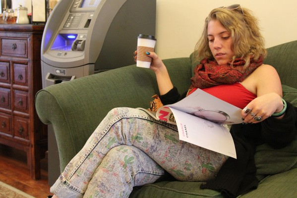 """A young woman enjoys her coffee while reading """"Nylon"""" magazine at Borderlands Cafe."""