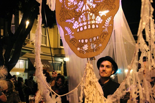 A man holding a skull walks down 24th Street as part of the Day of the Dead procession.