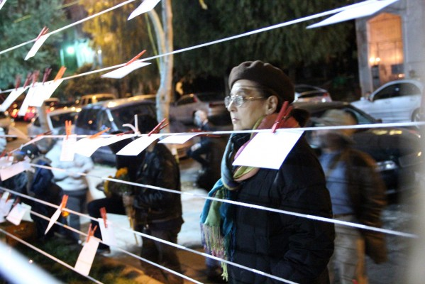 A woman stops to look at papers as part of a Day of the Dead memorial. People of all ages stopped to write messages to their dearly departed.