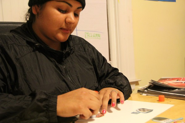 Dora Gutierrez works on a life map during a check-in for Young Queens Wednesday evening.