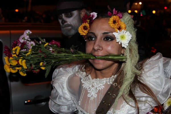 A girl clenches flowers in her mouth while retying a bow on her dress.