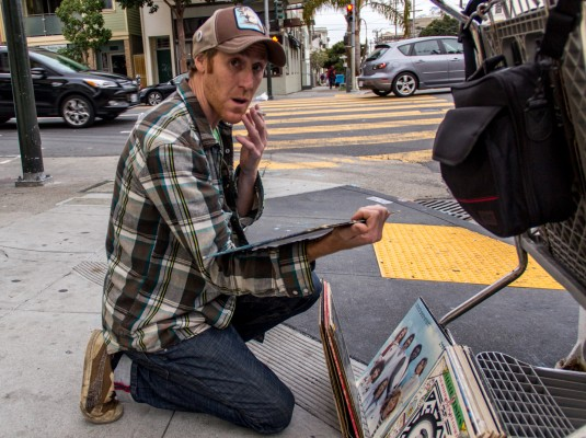 A man considers a stack of vinyl albums--each on sale for $1.