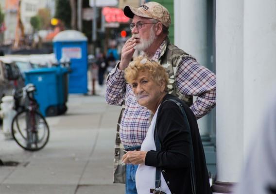 A couple takes a smoke outside an empty storefront.