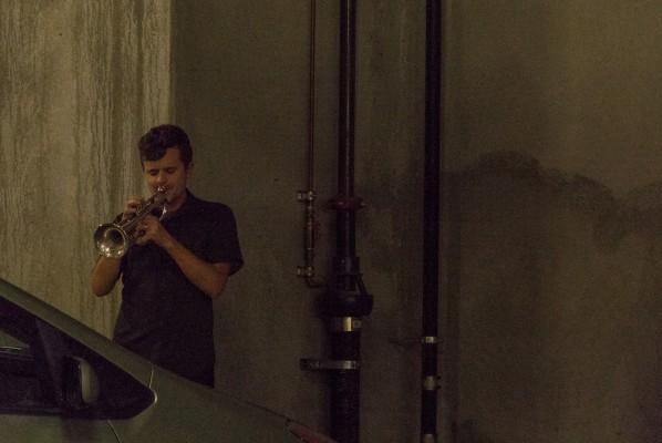 A man plays a trumpet in a cavernous Walgreens parking lot.