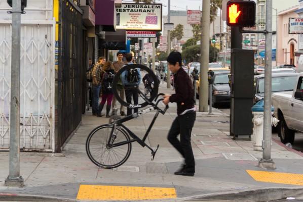A man wheels his bike down a Mission sidewalk.