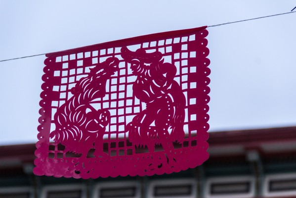 Mexican papel picado hangs on a long line on the street.