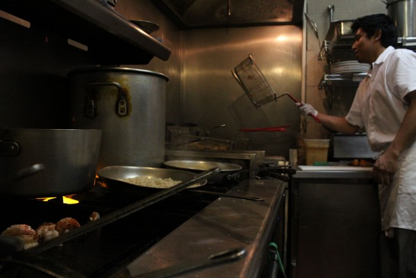 A cook prepares food in the kitchen.
