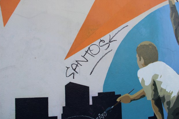 """a mural of a boy painting with the graffitied word, """"santos"""" above"""