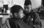 """Local hairstylist and DJ works his magic at a """"free cut"""" event at Cesar Chavez Elementary last year. Photo by Elliott Ten."""