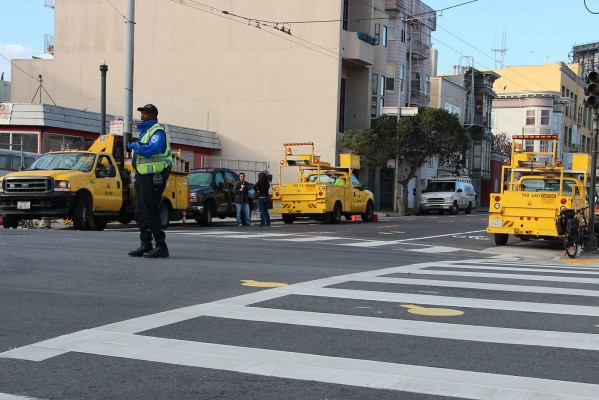 SFMTA workers direct traffic on the corner of 17th and South Van Ness streets. Photo by Yousur Alhlou.