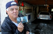 Samuel Picaso holds a photo from last year's flooding in his garage.