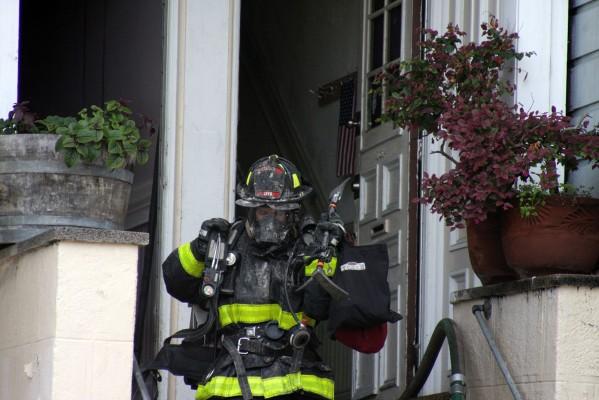 A firefighter exits 763-765 Capp Street.