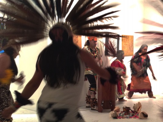 Traditional Mayan dancers perform around a drummer.